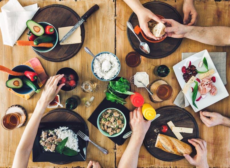 Взгляд сверху, группа людей сидя на таблице имея еду стоковое фото rf