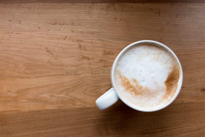 Взгляд сверху кофейной чашки на предпосылке деревянного стола стоковое фото