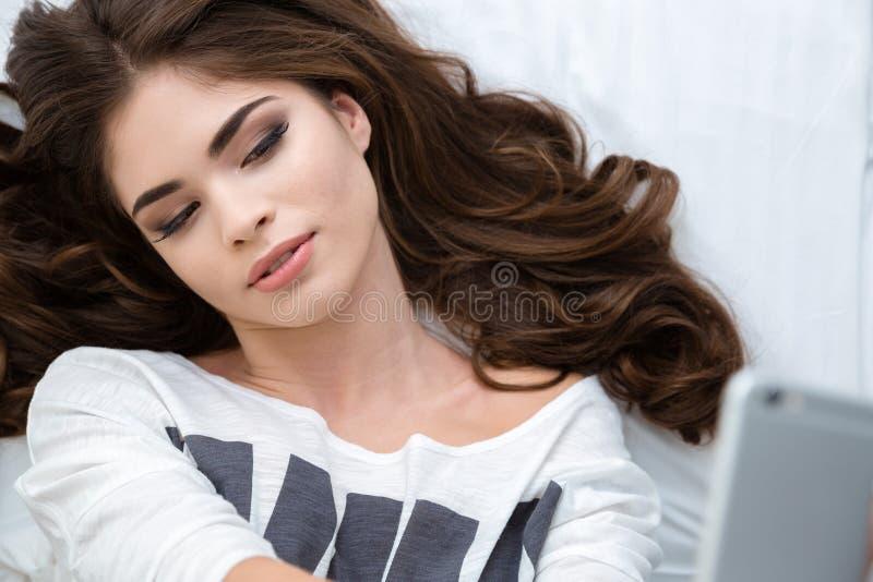 Взгляд сверху красивой лежа женщины принимая selfie с smartphone стоковое фото rf