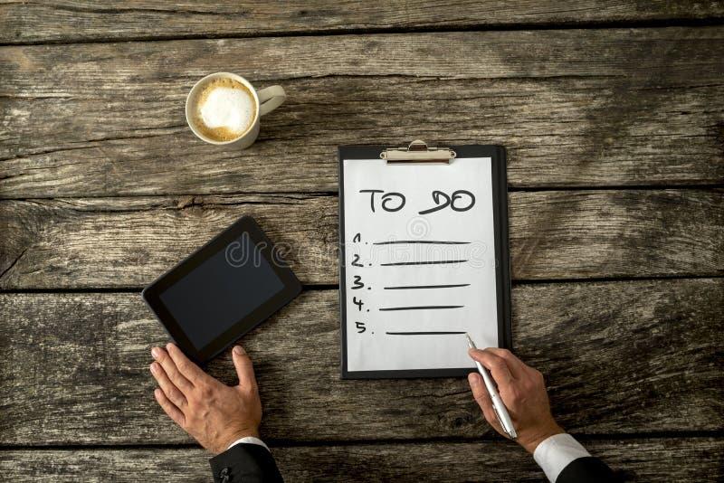 Взгляд сверху мужской руки писать a для того чтобы сделать список на белом листе p стоковое изображение