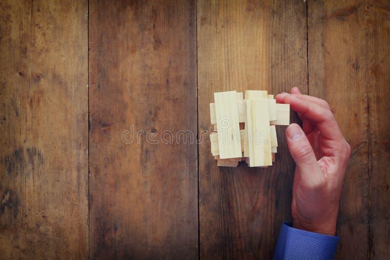 Взгляд сверху мужской руки устанавливая деревянный блок на башне концепция строгать и стратегии стоковые фото
