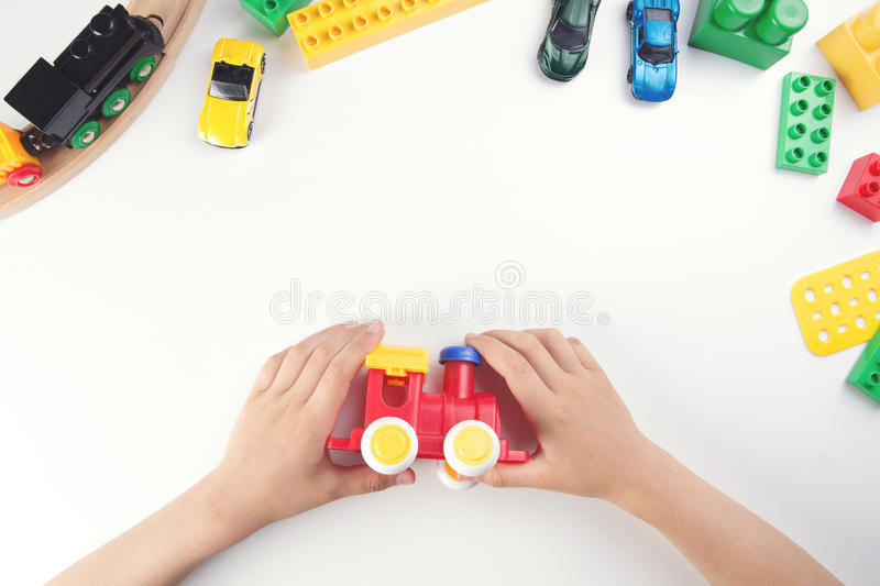 Взгляд сверху на руках ` s ребенка играя с поездом игрушки и много игрушек на белой предпосылке таблицы стоковое фото rf