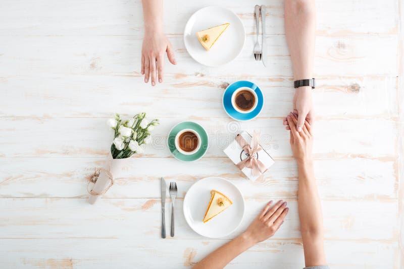 Взгляд сверху пар есть десерт и держа руки стоковые фотографии rf