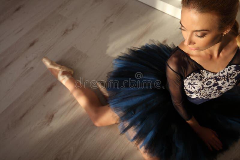 Взгляд сверху профессиональной балерины в голубых ботинках балетной пачки и pointe сидит на поле Copyspace стоковое изображение