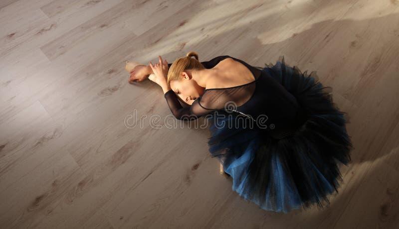 Взгляд сверху профессиональной балерины в голубых ботинках балетной пачки и pointe сидит и протягивающ на поле Copyspace стоковое фото