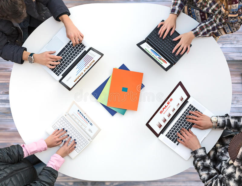 Взгляд сверху стола округленного белизной при 4 компьтер-книжки и руки людей печатая на клавиатуре стоковое фото rf