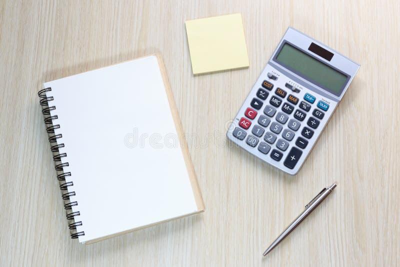 Взгляд сверху стола офиса с тетрадью, калькулятором, ручкой и примечанием стоковое изображение rf