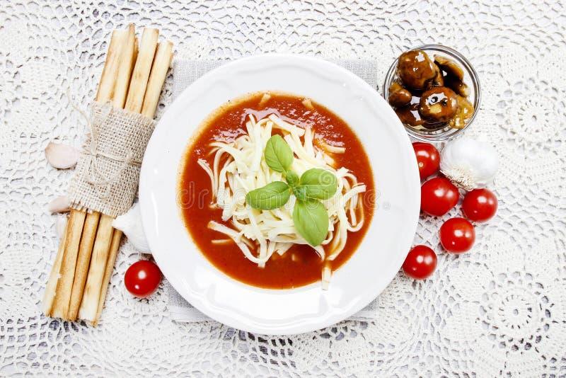 Взгляд сверху супа томата и стога breadsticks стоковые фото