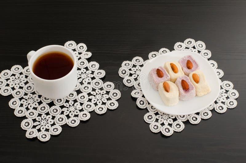 Взгляд сверху чашки кофе и красочное турецкое наслаждение с миндалинами на салфетках шнурка чернят таблицу стоковые фотографии rf