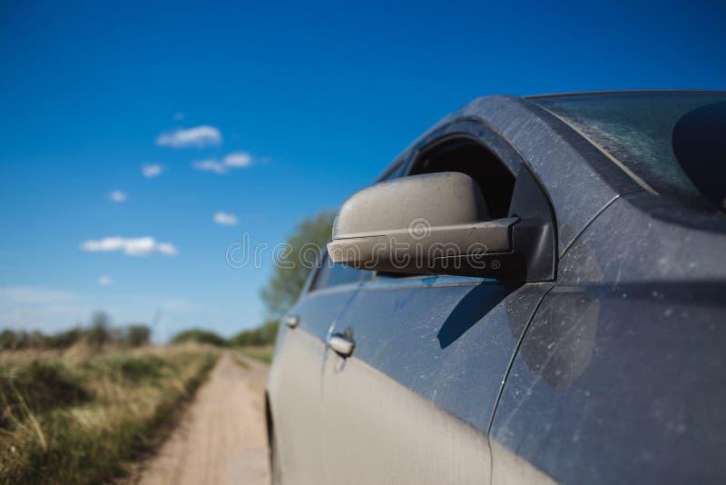 Взгляд со стороны автомобиля в пыли и blured поле лета на земной дороге стоковые изображения rf