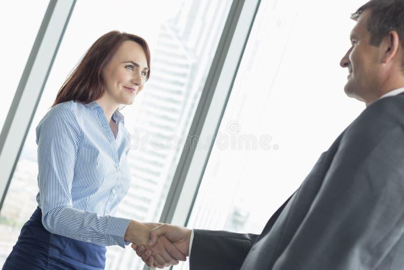 Взгляд со стороны бизнесменов тряся руки в офисе стоковое фото