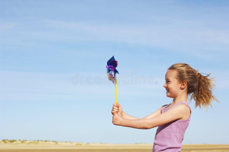 Взгляд со стороны девушки с Pinwheel на пляже стоковые фотографии rf