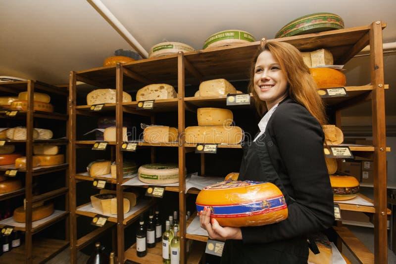 Взгляд со стороны женского продавца держа сыр в магазине стоковое фото