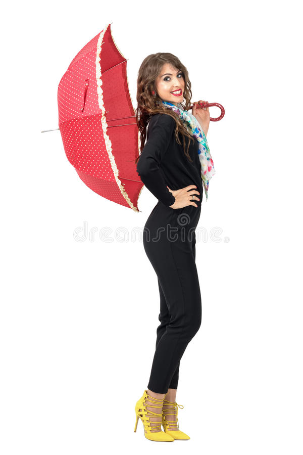 Взгляд со стороны женщины моды красоты в черном комбинезоне представляя с красным зонтиком стоковое фото rf