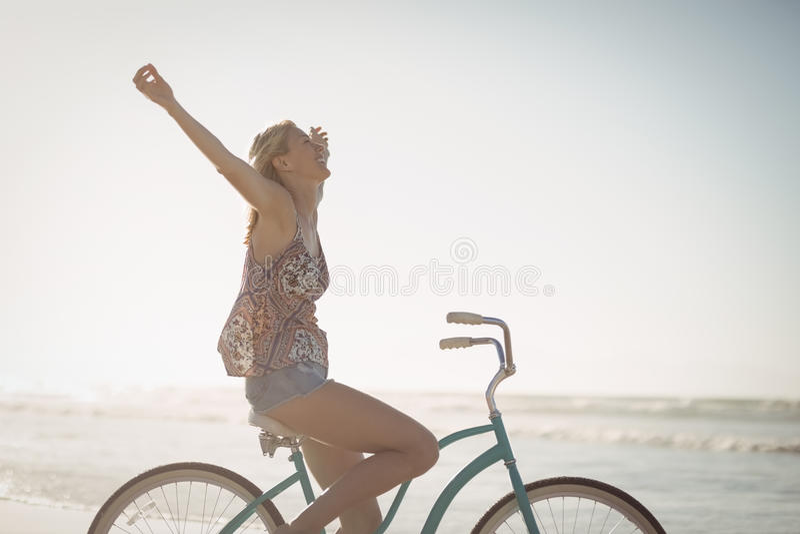 Взгляд со стороны жизнерадостного велосипеда катания женщины на пляже стоковое изображение