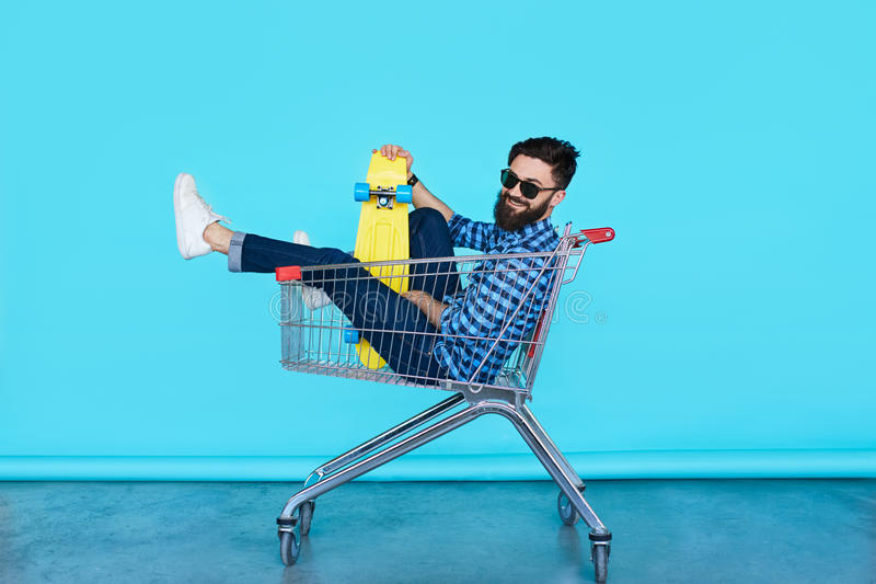 Взгляд со стороны жизнерадостного молодого человека сидя в магазинной тележкае стоковые изображения rf