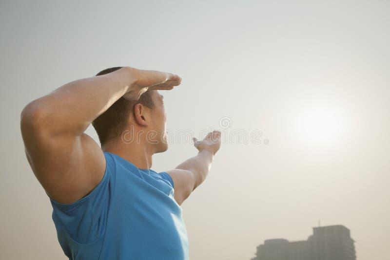 Взгляд со стороны молодого мышечного человека протягивая, рук поднял к небу в Пекине, Китаю стоковое изображение rf