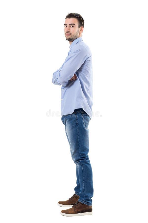 Взгляд со стороны молодого уверенно бизнесмена при пересеченные оружия смотря камеру стоковые изображения