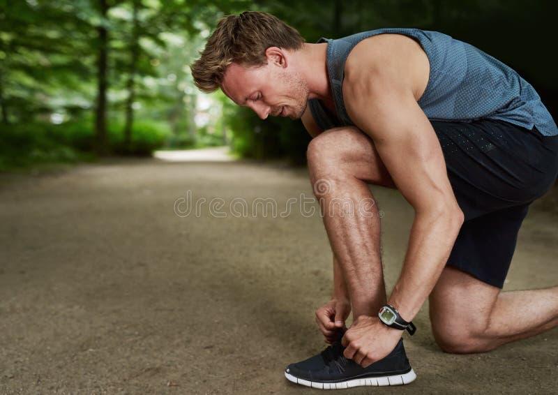 Взгляд со стороны молодого человека пригонки связывая шнурок стоковое фото