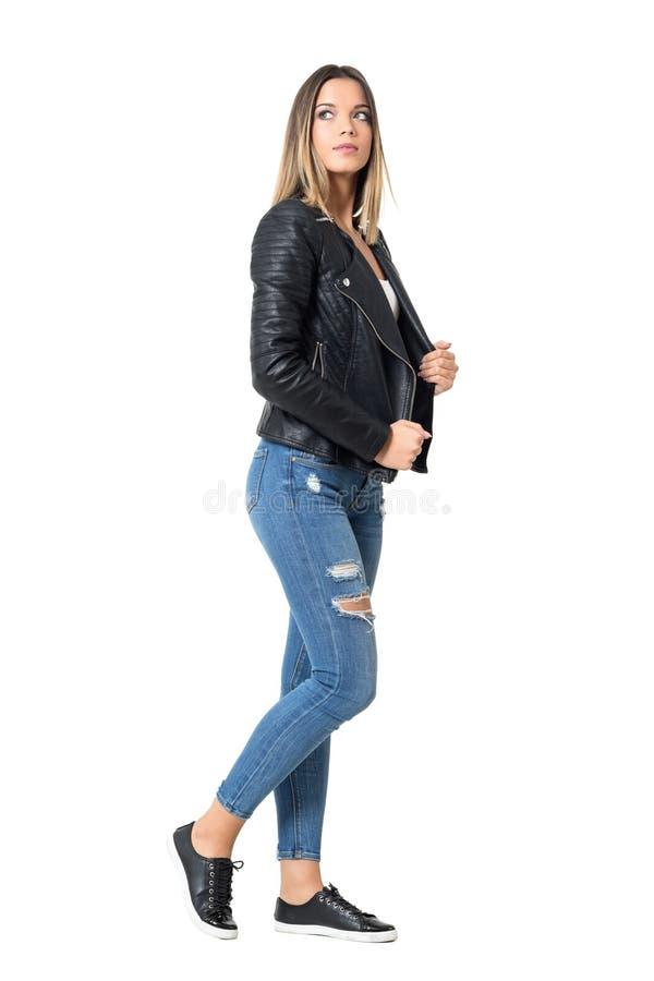 Взгляд со стороны молодой красивой женщины в сорванных джинсах и черной куртке смотря вверх стоковые фото