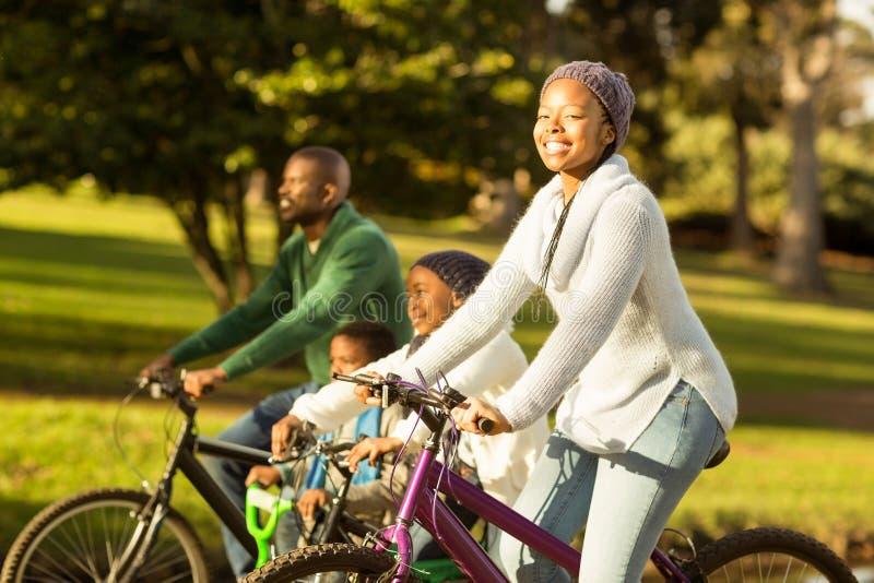 Взгляд со стороны молодой семьи делая езду велосипеда стоковая фотография rf
