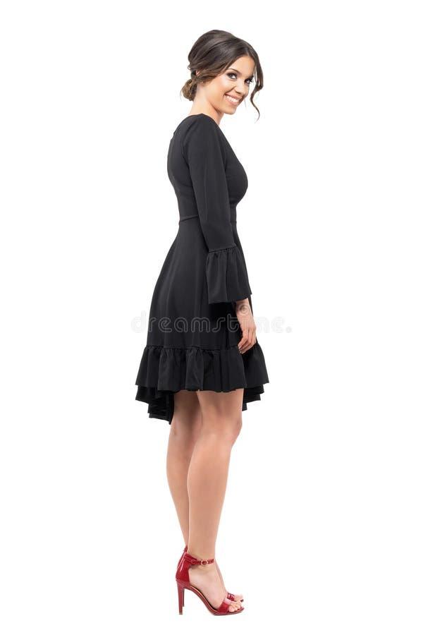 Взгляд со стороны счастливой расслабленной элегантной женщины в черном платье усмехаясь и смотря камеру стоковая фотография
