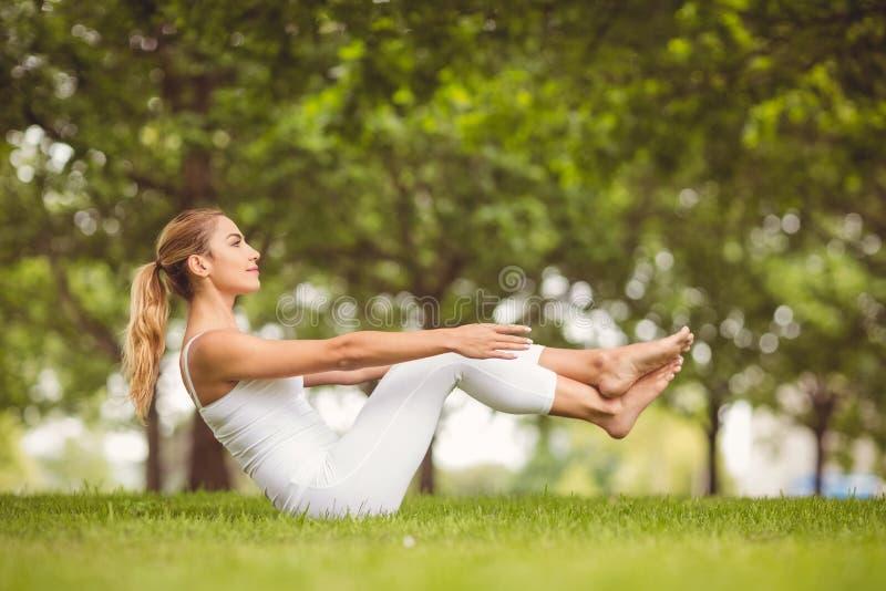 Взгляд со стороны уверенно женщины работая пока сидящ на траве стоковое фото rf