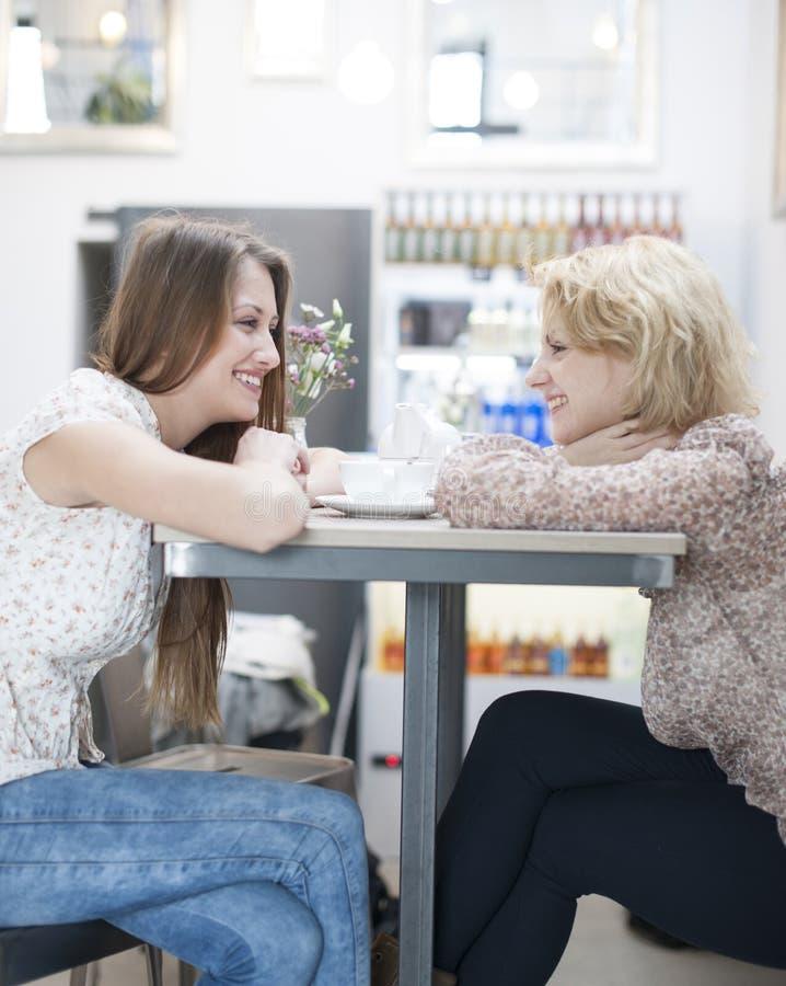 Взгляд со стороны усмехаясь молодых женских друзей сидя на таблице кафа стоковое фото rf