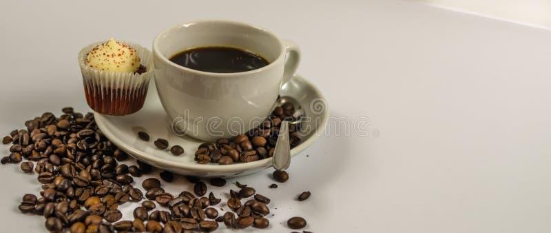 Взгляд со стороны черного кофе в белой чашке с cream булочкой, spil стоковые изображения