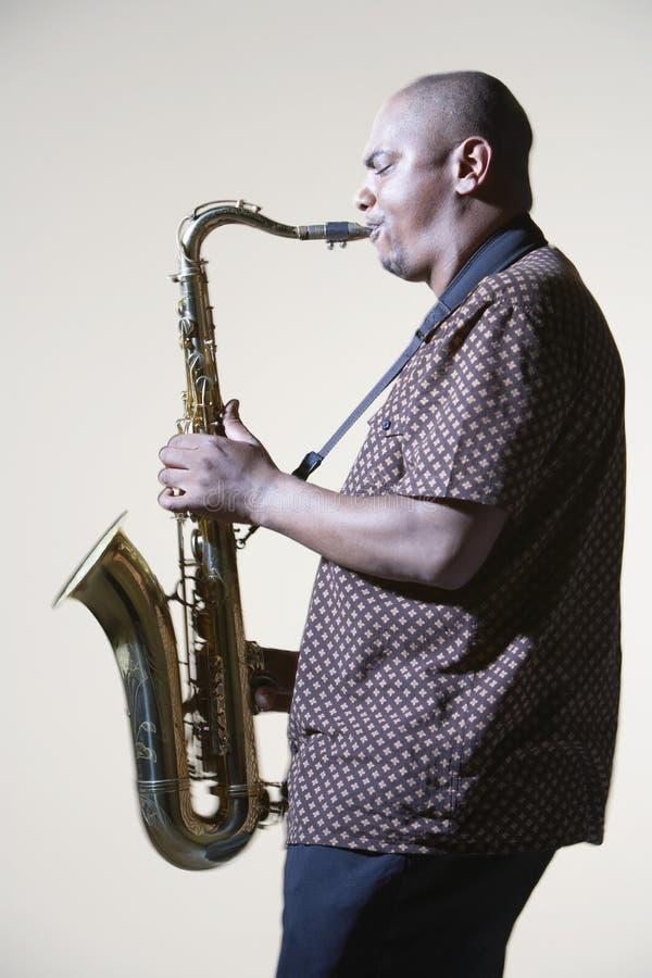 Взгляд со стороны человека играя саксофон стоковое изображение rf