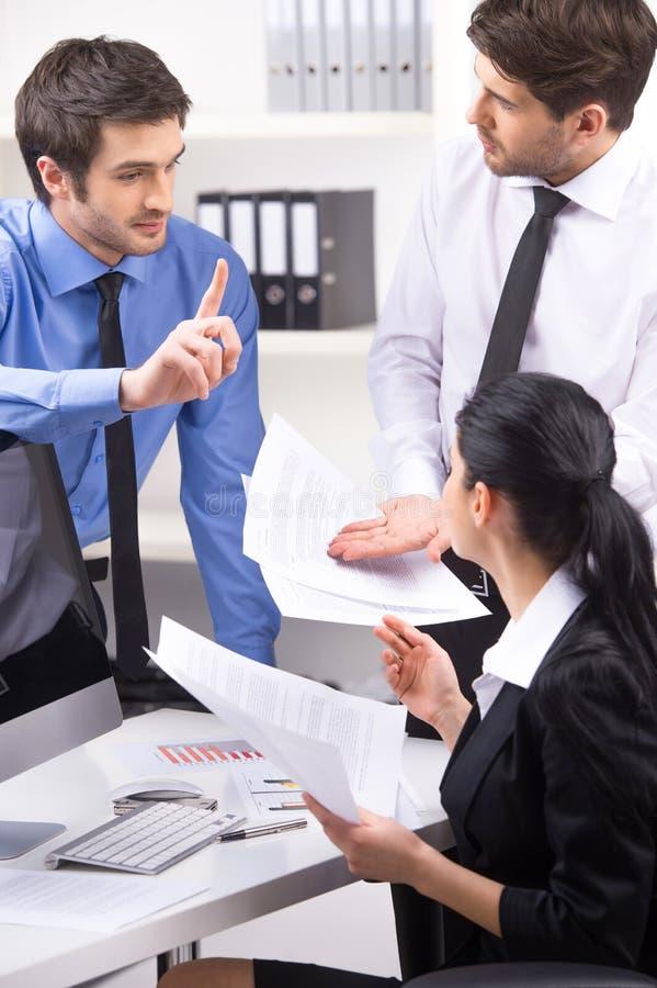 Взгляд со стороны 3 людей работая на компьютере на офисе стоковая фотография