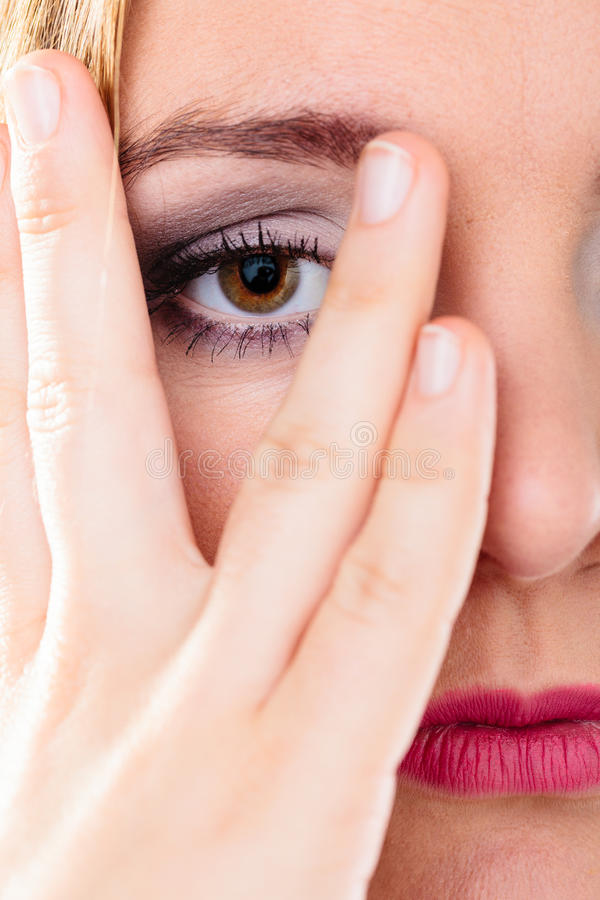 Взгляд стороны крышки женщины через пальцы стоковые фото