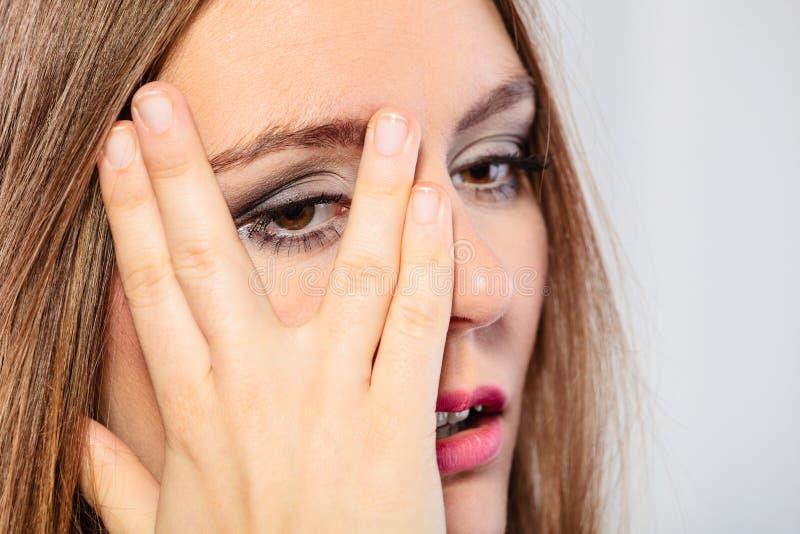 Взгляд стороны крышки женщины через пальцы стоковое изображение