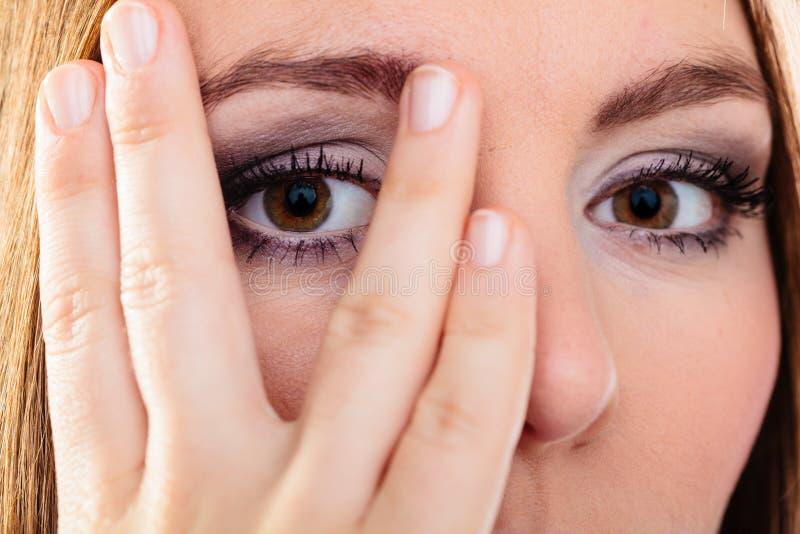Взгляд стороны крышки женщины через пальцы стоковые фотографии rf