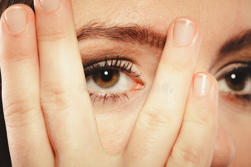 Взгляд стороны крышки женщины через пальцы стоковые изображения rf