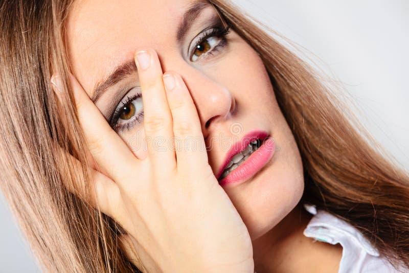Взгляд стороны крышки женщины через пальцы стоковые изображения