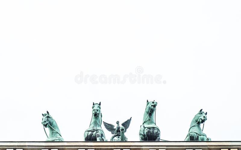 Взгляд строба Brandeburg бронзовых лошадей снизу на белой предпосылке стоковое фото