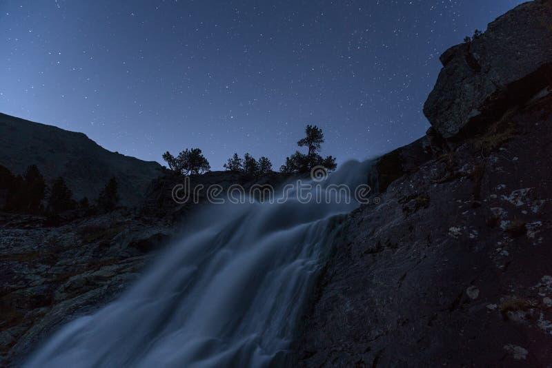 Взгляд с звездами на ясном небе, ландшафт ночи туманной долгой выдержки водопада предыдущий осени природы гористой местности гор  стоковые фото