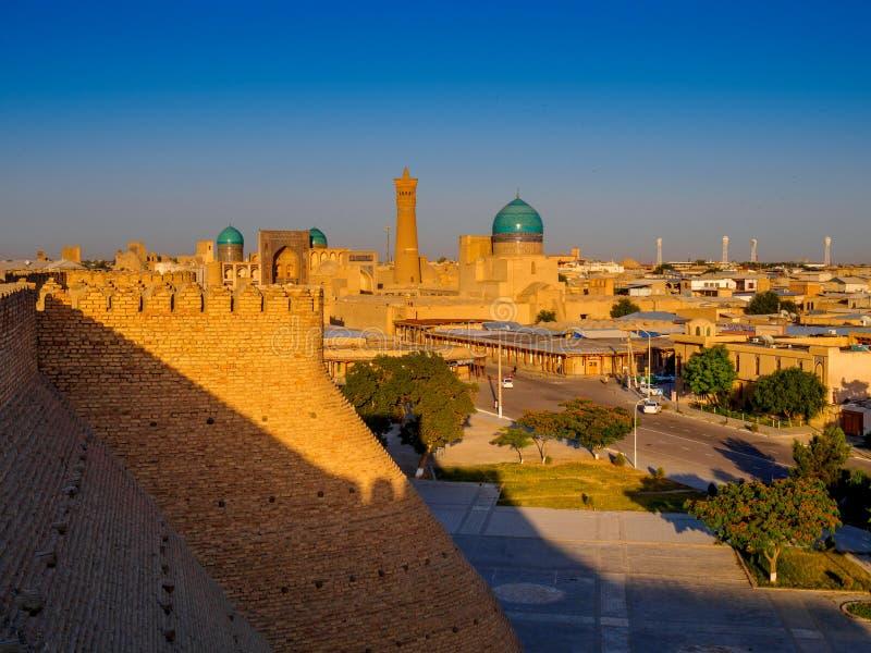 Взгляд сложного poi-Kolon с крепостью на заходе солнца, Бухарой ковчега, Узбекистаном Всемирное наследие ЮНЕСКО стоковые изображения