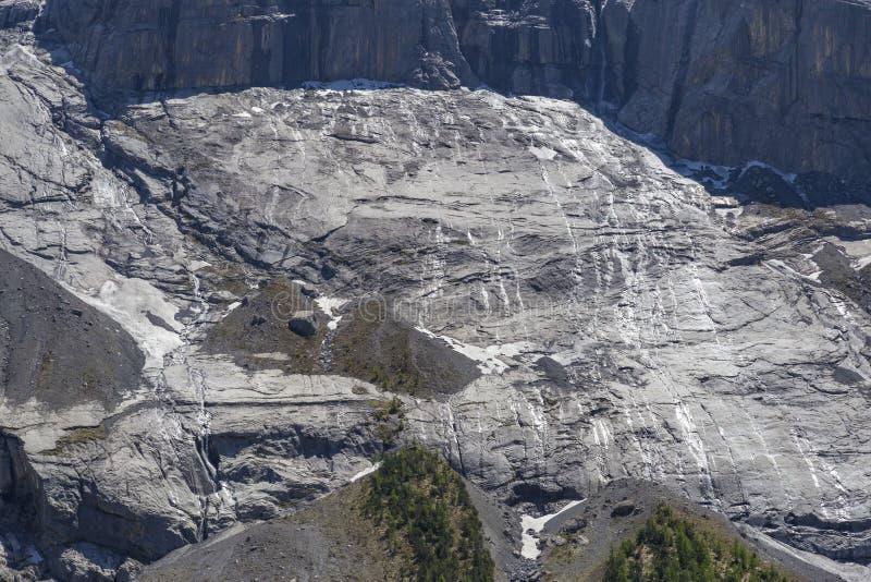 Взгляд утесов горы и плавя снега в швейцарце Альпах около Oeschinensee (озера Oeschinen), на Bernese Oberland, Швейцария стоковое фото rf