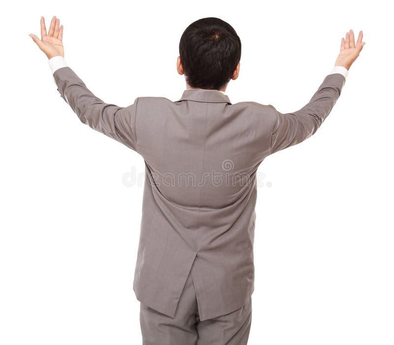 Взгляды бизнесмена назад быть поднятыми руками вверх стоковая фотография