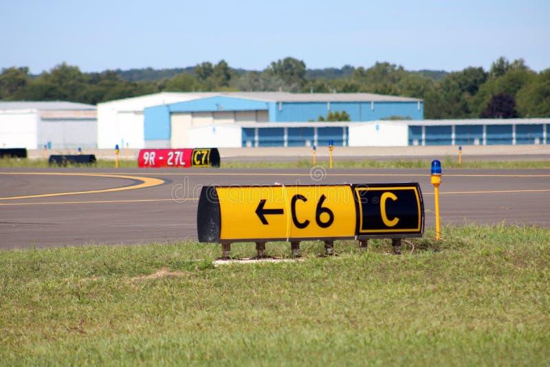 Взлётно-посадочная дорожка авиапорта подписывает авиаполе ангаров стоковые фото