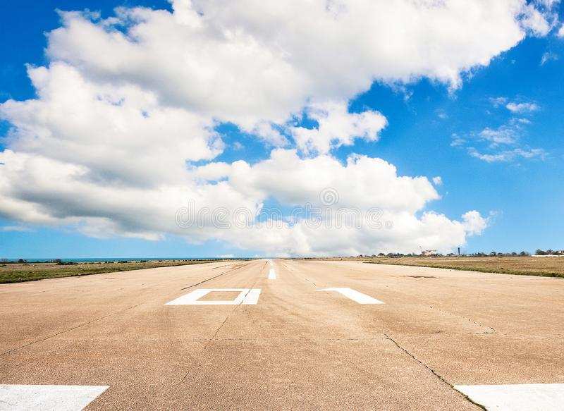 Взлётно-посадочная дорожка, взлётно-посадочная полоса в крупном аэропорте с маркировкой на голубом небе с предпосылкой облаков Ко стоковые фотографии rf