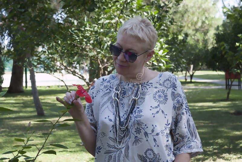 Взрослая женщина в солнцезащитных очках стоит рядом с кустом шиной розы стоковые фото