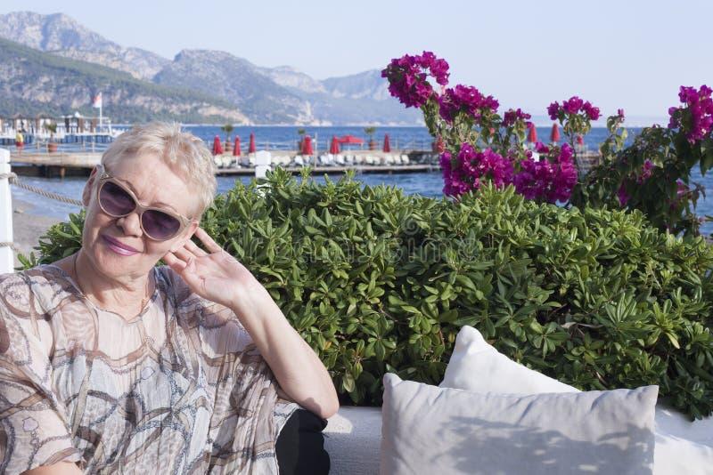 взрослая женщина в солнцезащитных очках улыбается, сидя на фоне розовых цветов и моря стоковые фото