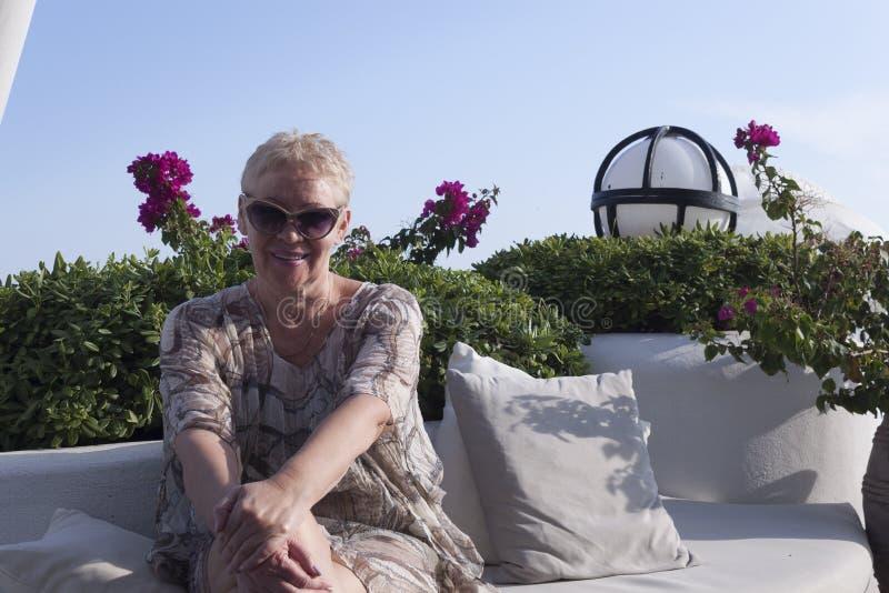 взрослая женщина в солнцезащитных очках улыбается, сидя на фоне розовых цветов стоковые изображения