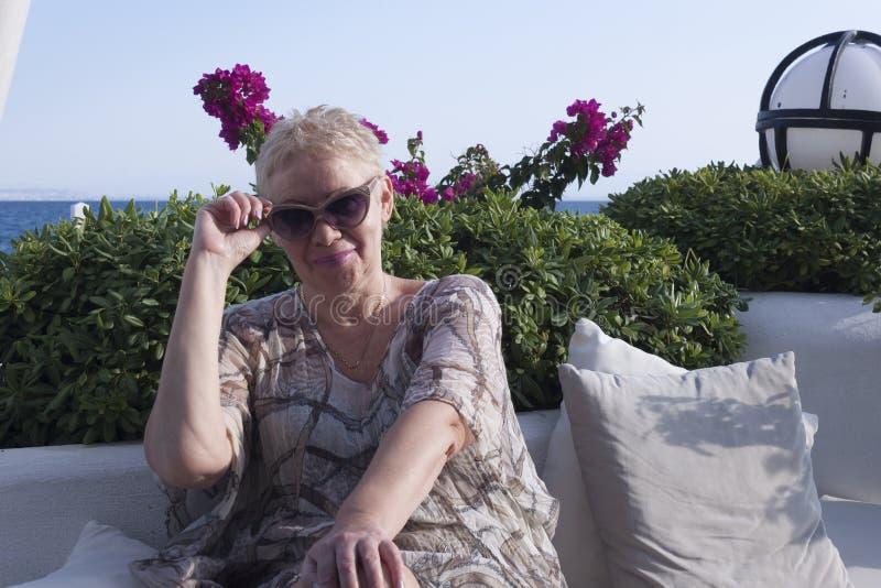 взрослая женщина в солнцезащитных очках улыбается, сидя на фоне розовых цветов и моря стоковое изображение rf