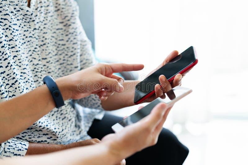 Взрослая женщина и дочь используя smartphone с пустым экраном Женщина указывая на дисплей мобильного телефона стоковые изображения rf