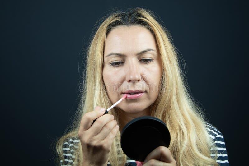 Взрослая женщина кладя некоторую губную помаду на ее губы Составьте внутри помещения стоковое фото rf