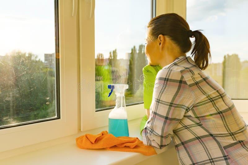 Взрослая женщина моет окна, убирая дом, взгляды женщины в чистое помытое окно стоковая фотография rf